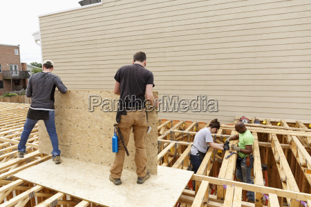 volunteers holding plywood at construction site
