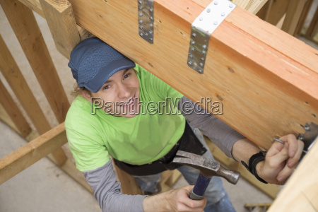 caucasian man hammering nail at construction