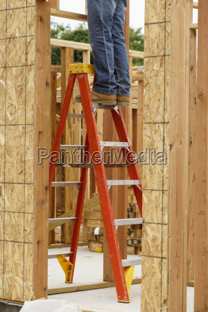 legs of caucasian man on ladder