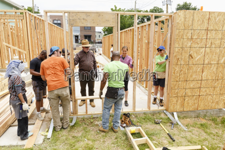 volunteers holding wall at construction site