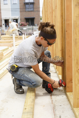 caucasian woman drilling lumber at construction