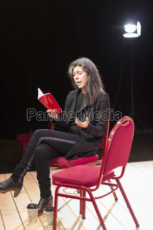 hispanic woman reading script on theater