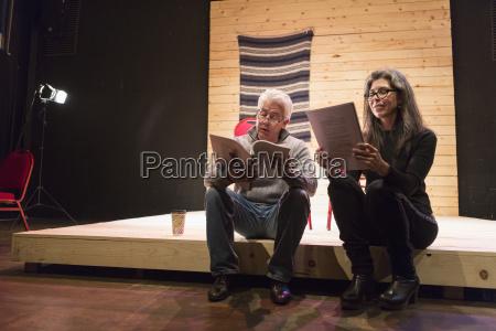 hispanic man and woman reading scripts