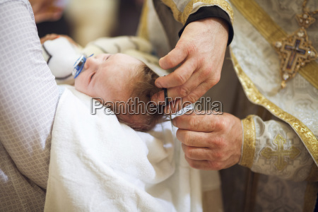 priest clipping hair of baby girl