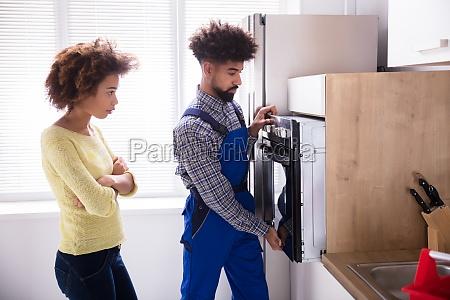 technician examining oven in kitchen