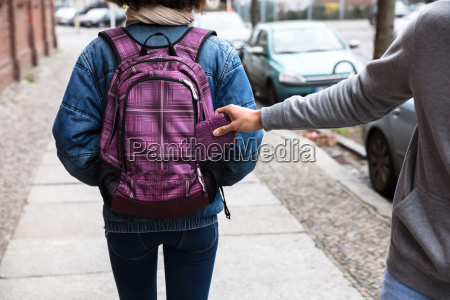 thief stealing purse from backpack
