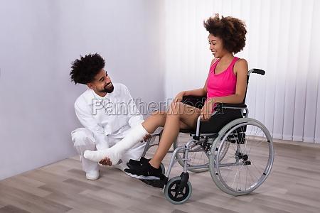 physiotherapist examining leg of female patient