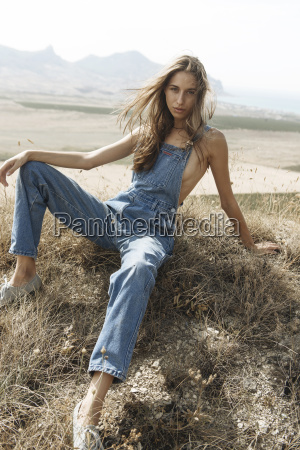 caucasian woman wearing overalls sitting in