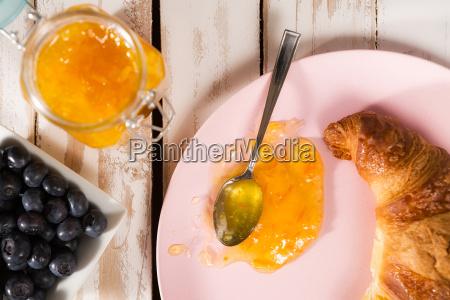 closeup of croissant and orange jam