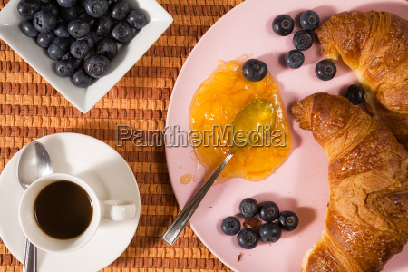 closeup of croissant blueberries coffee and