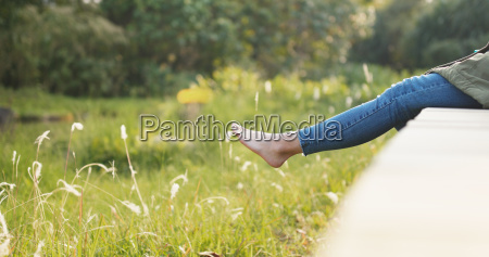 woman sitting on wooden path under