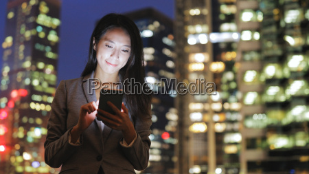business woman using cellphone in city
