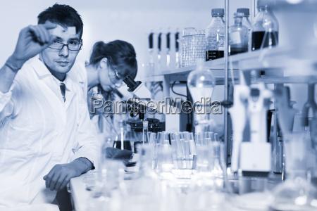 health care professionals microscoping in scientific