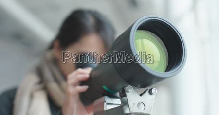 woman looking though the telescope