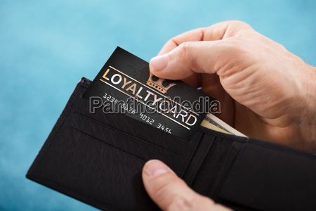 person removing loyalty card from wallet
