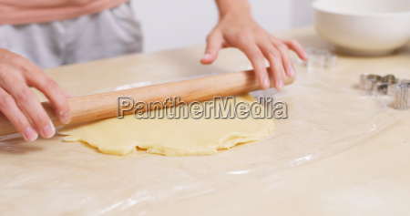 chef rolling dough with rolling pin