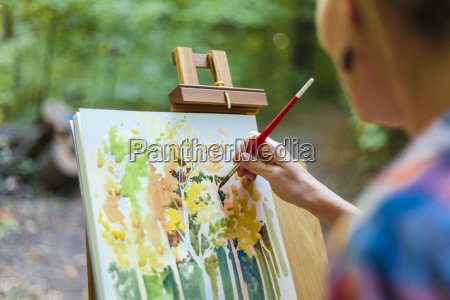 female painter creating watercolor painting in