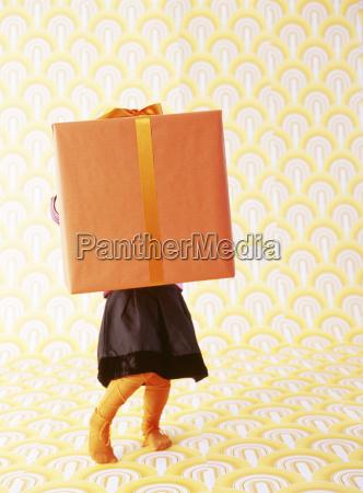 little girl behind oversized christmas present
