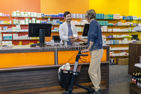 pharmacist giving medicine to customer with