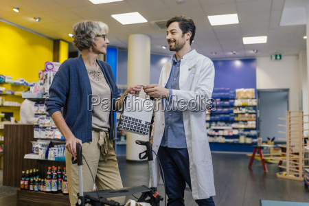 pharmacist giving bag of medicine to