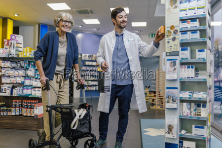 smiling pharmacist and customer with wheeled