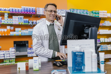 smiling pharmacist talking on phone at