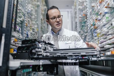 pharmacist examining commissioning machine in pharmacy