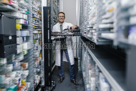 smiling pharmacist with commissioning machine in