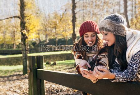 two pretty women using smartphone in