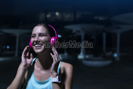 happy young woman with pink headphones
