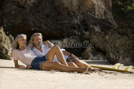 handsome senior couple with surfboard lying