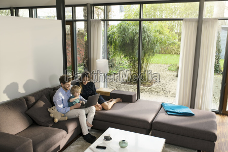 parents and son sitting on sofa
