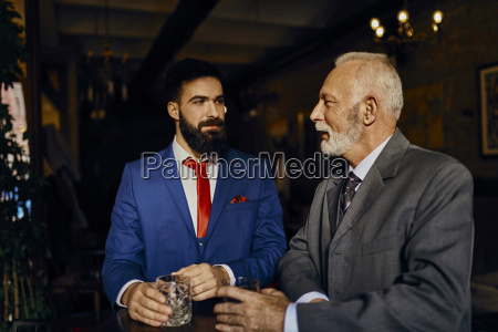 two elegant men in a bar