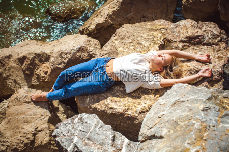 portrait young woman on stones near