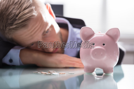 depressed man looking at coins and