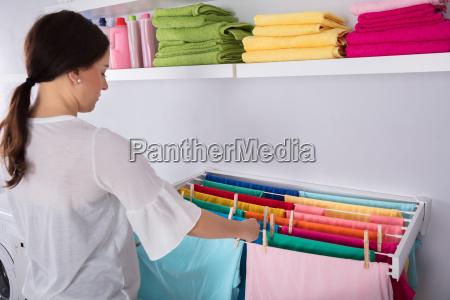 woman hanging wet clothes in laundry