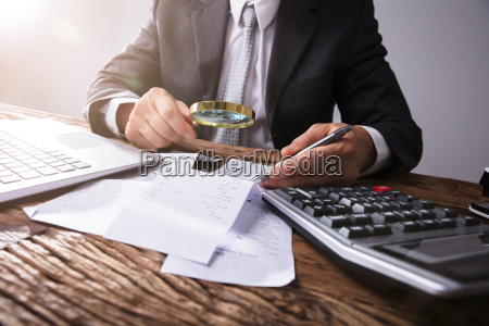 businessperson looking at receipts through magnifying