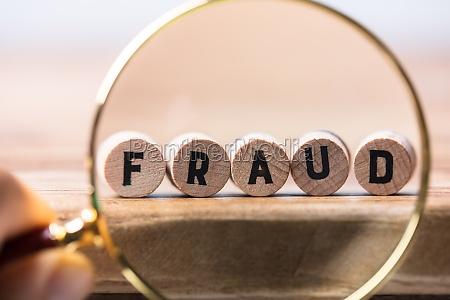 person examining fraud blocks through magnifying