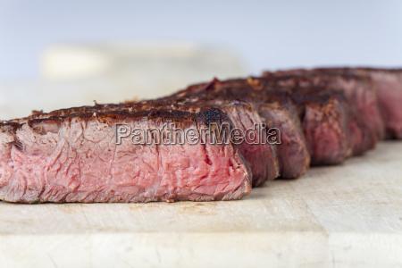 row of steak slices on wood
