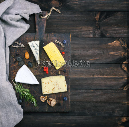 cheeses on a brown wooden board