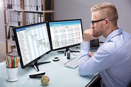 businessman looking at gantt chart on