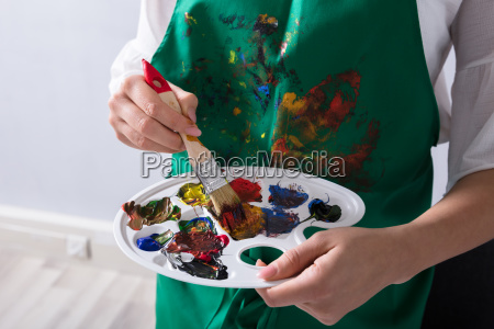 an artist holding paint palette and
