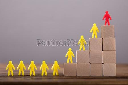 red figure leading human figures on