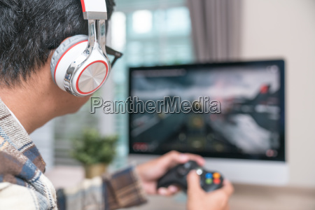 back view of young gamer playing