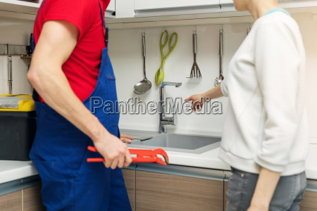 housewife showing broken water tap to