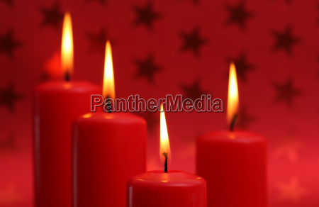 burning candles in front of red