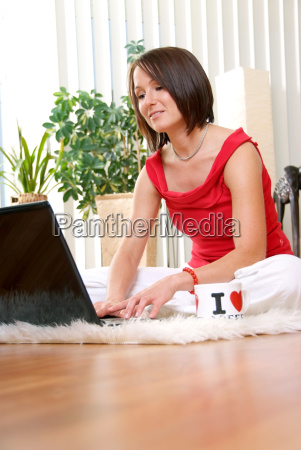 young woman with laptop sitting cosy