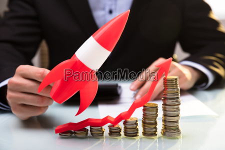 businessperson flying rocket over stacked coins