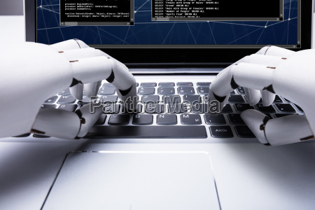 robot typing on laptop keypad