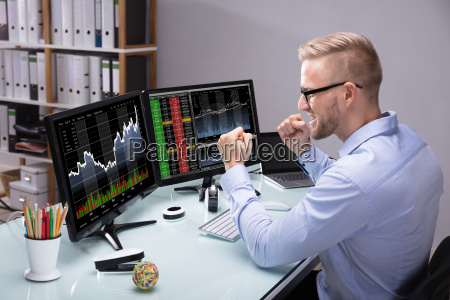 excited stock market broker looking at